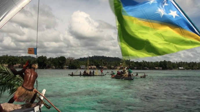 Climate Challenger flying the Solomon Island flag, cruises into Pere village after their 3 month long distance voyage. (photo: taken as a still from video)