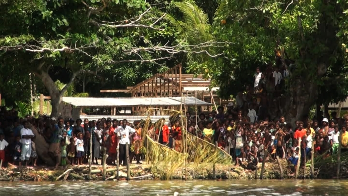 Villagers of Pere village wait on shore for the Climate Challenger and crew. (photo: still from video)